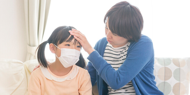 風邪を引いた娘と看病する母親