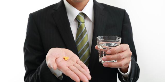 薬を飲む男性