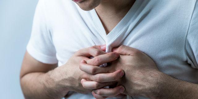 心臓を押さえる男性