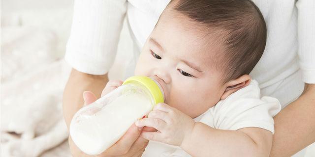 哺乳瓶でミルクを飲ますママ
