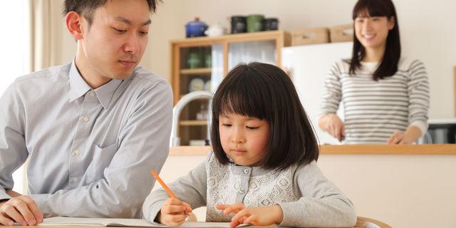 勉強を娘に教えるパパを見守るママ