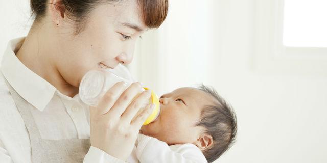 赤ちゃんにミルクをあげるスタッフ