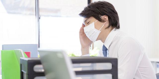 風邪で仕事する男性