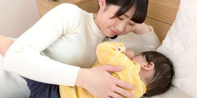 子どもに添い寝する母親