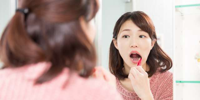 鏡を見ながら歯磨きする女