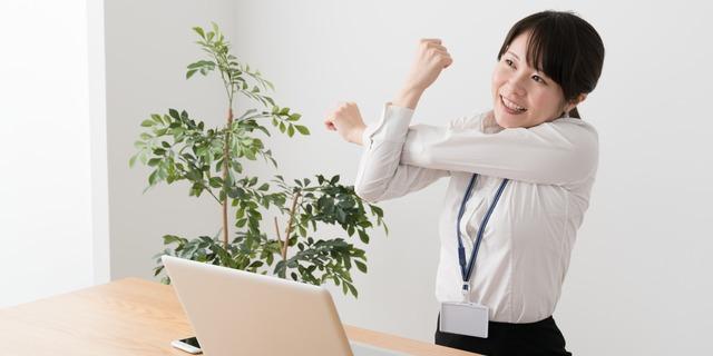 オフィスでストレッチする女性