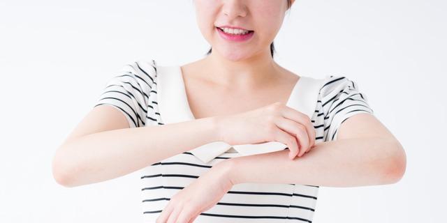 腕をかく女性
