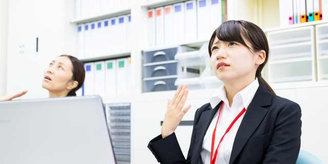オフィスの暑さに苦しむ女性