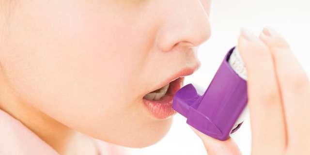 喘息症状で吸入する女性